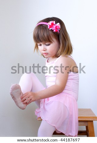 Little ballerina dancer putting on her shoe - stock photo