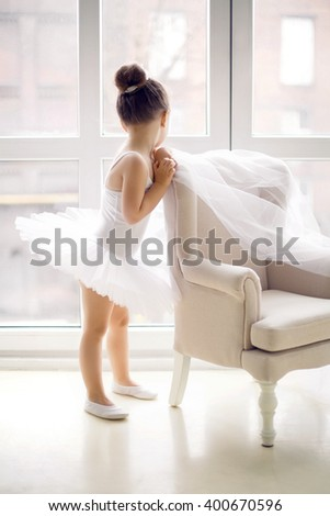 little ballerina girl 2 years in the Studio in a white tutu dress clothes is the chair and looking out the window - stock photo
