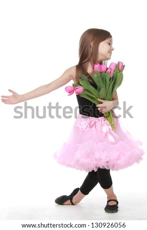 Little ballerina with long healthy hair in a pink tutu dancing ballet with tulips - stock photo