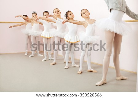Little ballerinas dancing with ballet teacher in dance studio. Teacher doing exercise, and little ballerinas is watching and following her movements while using stick on the wall - stock photo
