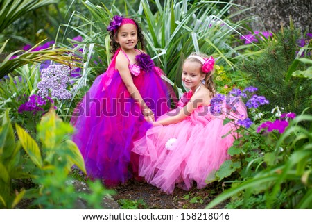 Little ballerinas playing in a garden. - stock photo