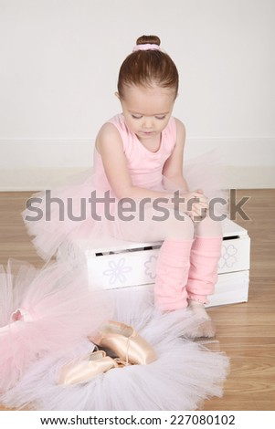 Little ballet girl trying on shoes at the ballet studio - stock photo