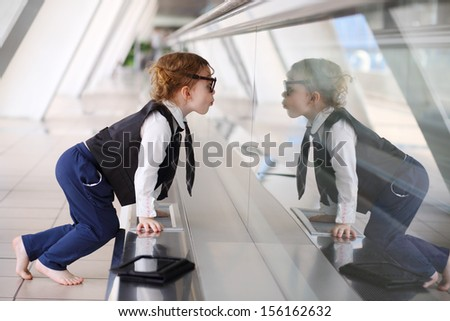 Little barefoot girl sits on floor in gallery near glass wall and stares at her reflection. - stock photo