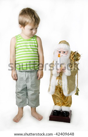 Little barefooted Boy and toy Santa Claus