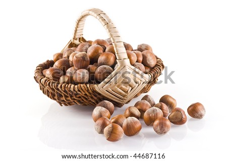 Little basket filled with hazelnuts on a white background. - stock photo