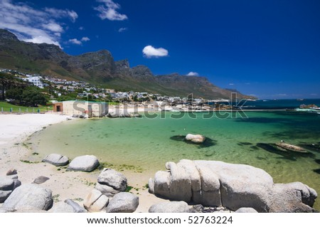 Little bay near the beach of camps bay with a marvelous emerald sea and the twelve apostles mountain in the background - stock photo
