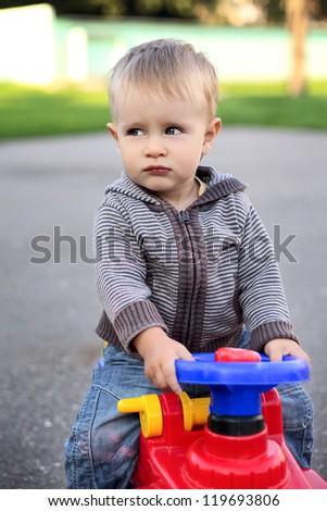 little beautiful baby boy in car - stock photo