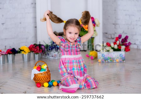 little beautiful baby girl playing in the room next to Easter eggs