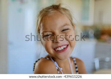 Little beautiful blonde smiling girl poses faces closeup. - stock photo