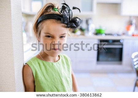 Little beautiful dissatisfied girl in a green dress on a background of the kitchen.