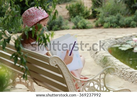 Little beautiful girl child draws with crayons in the album outdoors - stock photo