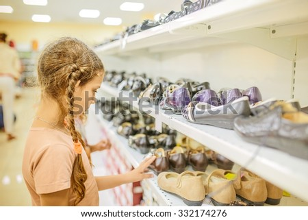 Little beautiful girl chooses shoes at a store. - stock photo