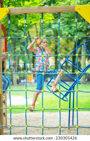 Little beautiful girl climbs on rope harness in summer city park. - stock photo