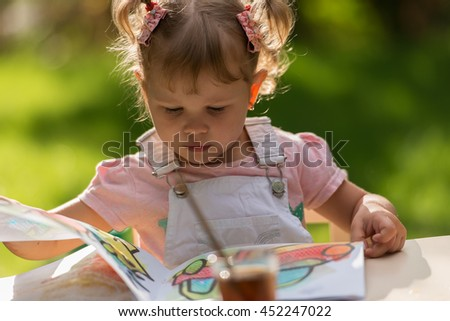 Little beautiful girl draws paints in the yard on a background of grass and trees - stock photo