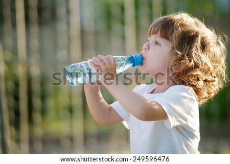 little beautiful girl drinking clean water from plastic bottle - stock photo