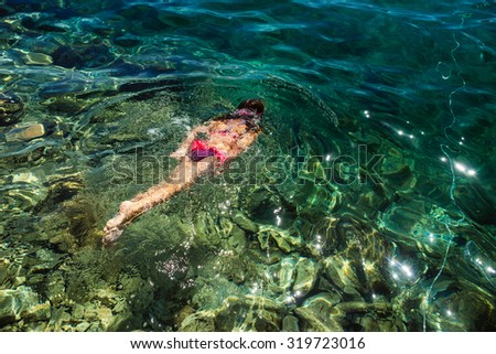 Little beautiful girl floating in the Adriatic Sea. - stock photo
