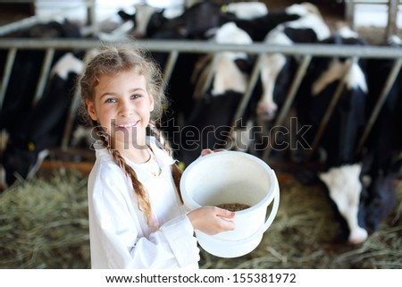 Little beautiful girl holds white bucket with food and smiles in stall with many cows. - stock photo