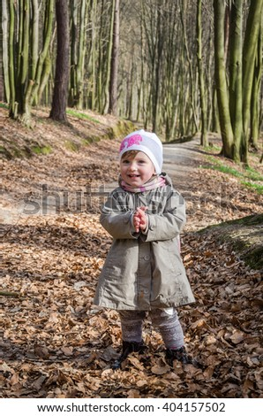 Little beautiful girl in a baby raincoat, hat and scarf is played in spring forest dry leaf litter throwing their smiles in a good playful mood - stock photo