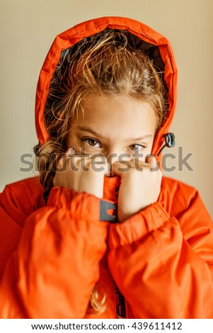 Little beautiful girl in a red jacket with a hood up close. - stock photo
