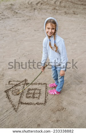 Little beautiful girl in hood draws in sand image of house.