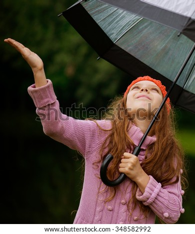 Little beautiful girl in red cap and an umbrella on background of autumn park with lake. - stock photo