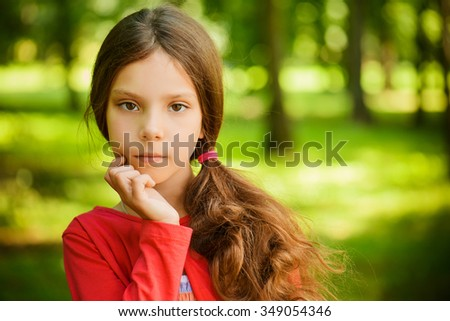 Little beautiful girl in red clothes thought, against green summer park. - stock photo