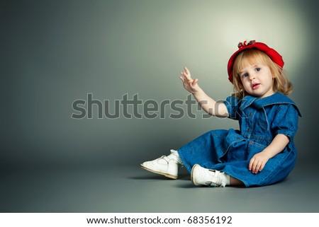 little beautiful girl in red hat. Studio shot. - stock photo