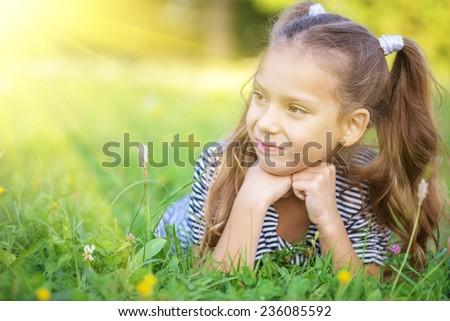 Little beautiful girl lies on green grass, sun summer in city park. - stock photo