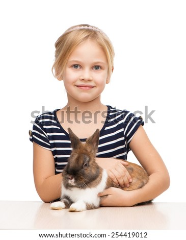 Little beautiful girl looking at camera and holding brown bunny, isolated on white