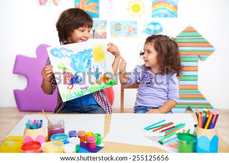 Little beautiful girl looking at finished drawing of boy and showing thumb up. Lesson in preschool center for children - stock photo