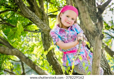 Little beautiful girl looks sitting in a tree on a walk in the park on a sunny warm summer day.