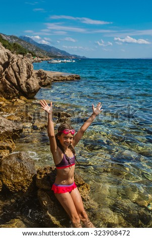 Little beautiful girl near the beach of Adriatic Sea. - stock photo