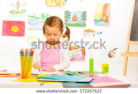 Little beautiful girl on craft lesson painting and cutting color paper - stock photo