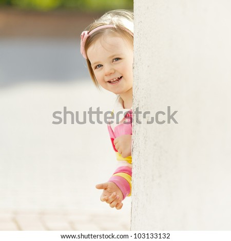 little beautiful girl peeping from behind the wall - stock photo