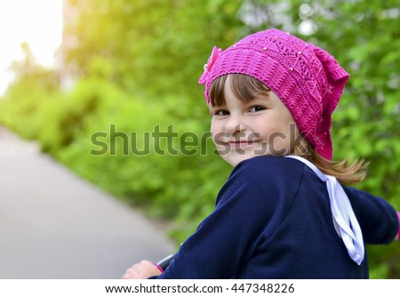 Little beautiful girl riding her bike in the Park - stock photo