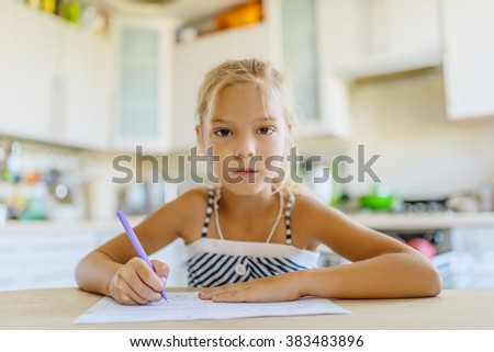 Little beautiful girl sitting at the kitchen table and writing with a ballpoint pen in a notebook. - stock photo