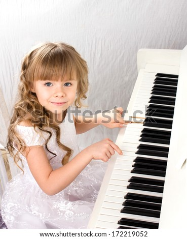 little beautiful girl with blond long curls in white fashion dress playing on white piano  - stock photo