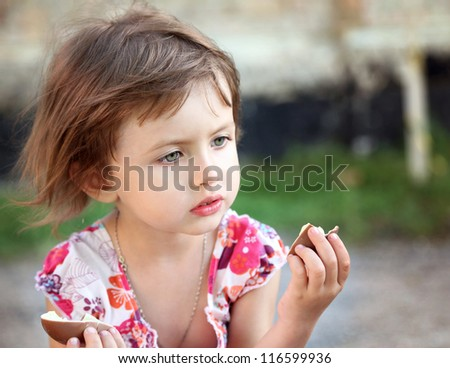 little beautiful girl  with chocolate in park - stock photo