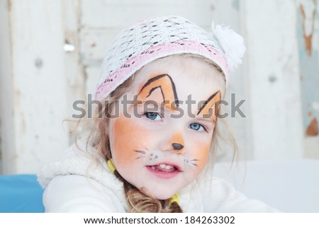 Little beautiful girl with face painting of orange fox poses in hat - stock photo