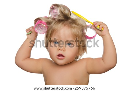 Little beautiful girl with hair curlers and comb isolated on white - stock photo