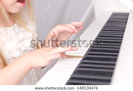little beautiful girl with opened mouth playing on piano, closeup - stock photo