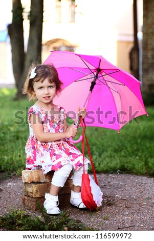 little beautiful girl  with pink umbrella in park