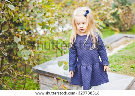 Little beautiful girl with small blue bow in blonde hair wearing blue dress in park during walk on sunny summer autumn day. Emotions on face. Copy space - stock photo