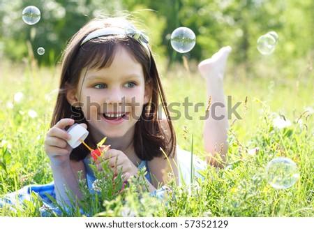 little beautiful happy girl blowing soap bubbles - stock photo