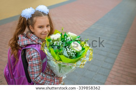 Little beautiful happy girl goes to school with a bunch of flowers. - stock photo