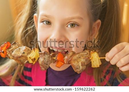 Little beautiful smiling girl eating kebab restaurant. - stock photo