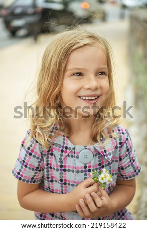 Little beautiful smiling girl holding flower, summer in city park. - stock photo