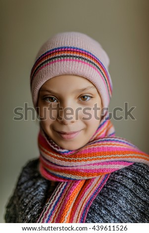 Little beautiful smiling girl in a cap and a scarf closeup. - stock photo