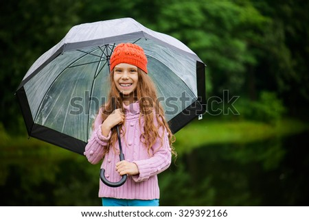 Little beautiful smiling girl in a red cap and pink sweater holding umbrella on a background of green park. - stock photo