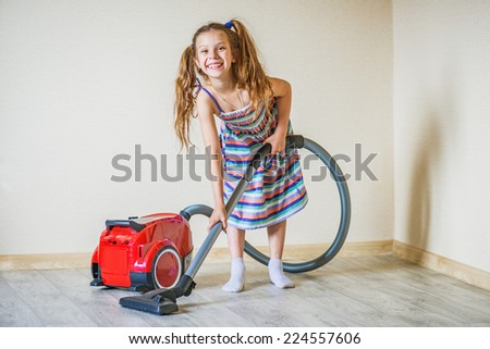 Little beautiful smiling girl running with vacuum cleaner at home. - stock photo
